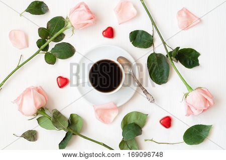 Romantic flat lay - cup of coffee peach roses and heart shaped candies,romantic love background. Romantic morning concept. Romantic love background. Love romantic concept in pastel tones