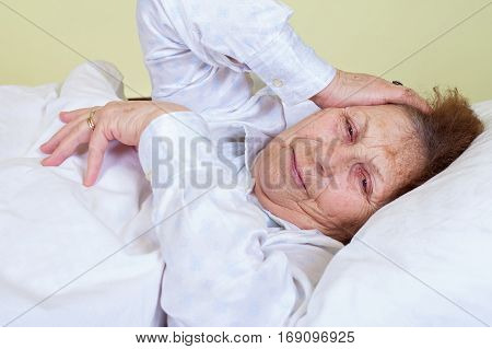 Picture of an elderly woman having a migraine lying in bed