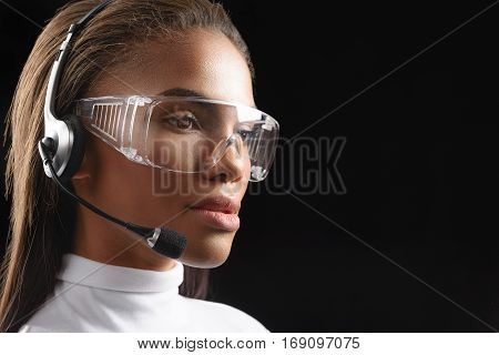Attentive call center woman is consulting client. She is wearing headset and glasses. Isolated and copy space in right side