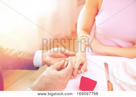 couple, love, engagement and holiday concept - close up of man putting ring to his fiance finger at restaurant