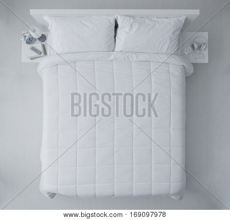 Elegant bedroom with white duvet and sheets top view