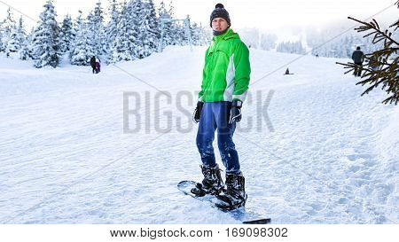snowboarder stands on the snowboard in the winter on a ski run in a green jacket
