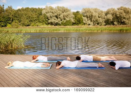 fitness, sport and healthy lifestyle concept - group of people making yoga exercises on river or lake berth