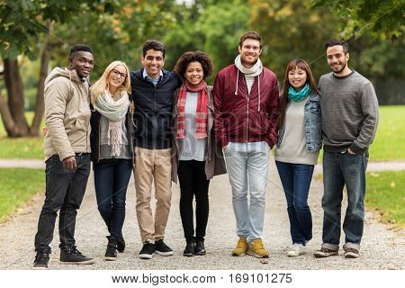 people, friendship, communication and international concept - group of happy friends at autumn park