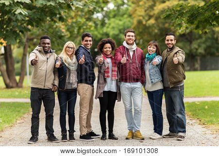 people, friendship, communication and international concept - group of happy friends showing thumbs up at autumn park