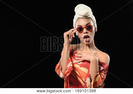 Fashionable young mulatto girl is expressing her shock. She is touching sunglasses and looking forward with scrutiny. Isolated and copy space in left side