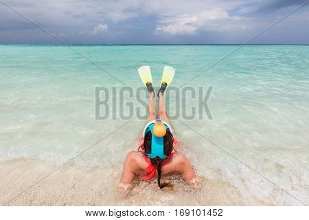Woman wearing snorkeling mask and fins ready to snorkel in the ocean, Maldives. Clear turquoise water.