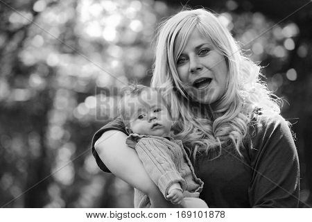 Angry mother defending her baby. Children abuse, domestic violence and neglected child concept. Story from wild divorce. Black and white photography.