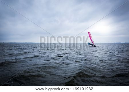 male windsurfer on a huge lagoon sailing towards the camera