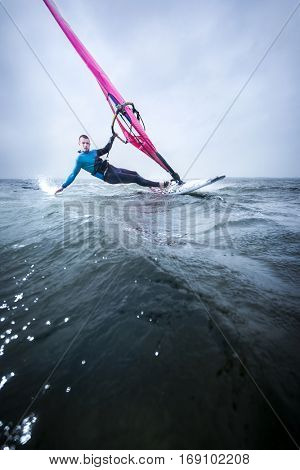 windsurfer hanging in the strong wind, gliding over the flat water