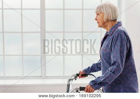 Calm old woman walking with foldable walker in bright white hospital corridor