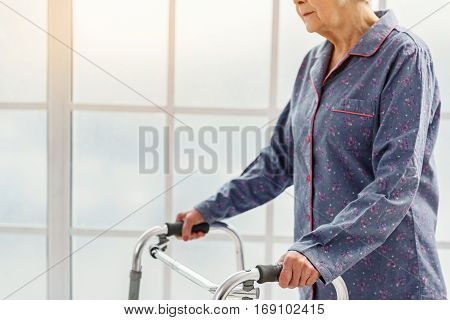 Serene retiree woman keeping on gutter frame while standing in bright hospital hall