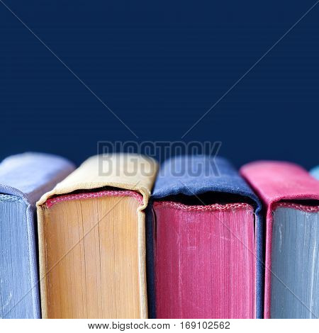 Colorful vintage book covers with colored spines and pages. macro view Soft focus. Dark blue background copyspace