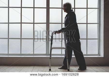 Unconcerned grannie wearing pajama keeping on walking frame while going in white hospital corridor near wide window