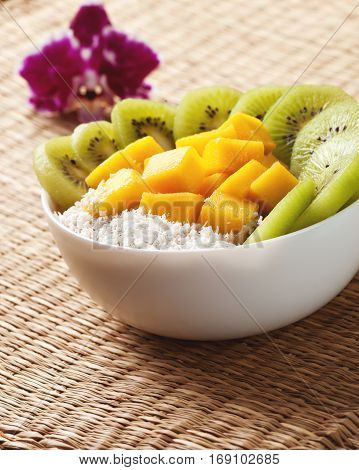 Fruit smoothie with mango kiwi fruit in a bowl on a straw background (top view)