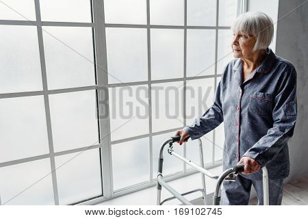 Serene retiree woman wearing night suit, holding on walking aid while looking at wide window in hospital
