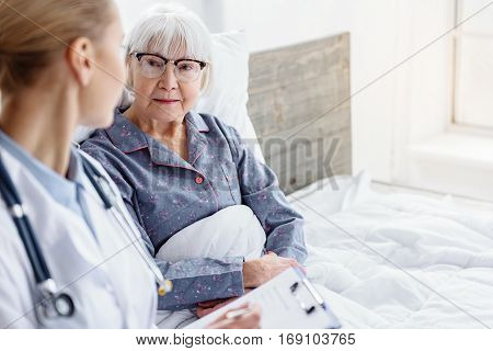 Focus on smiling kind grandmother lying on soft bed in white room of polyclinic. Doctor asking outgoing old woman about her health