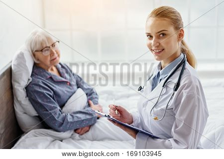 Happy kind doctor offering consultation of female pensioner in hospital room while holding tablet in her hand