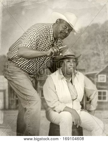 A senior African American couple together in an old western town.  He's pointing towards something.  She's trying to see what he's talking about.  Sepia toned and antiqued.
