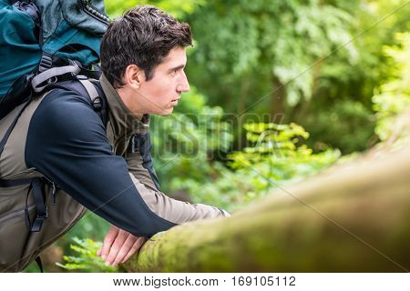 Young hiker man taking a breather and enjoying the view