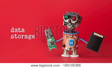 Data storage concept. Robot toy with usb flash stick and memory card on red background. Copy space macro view photo