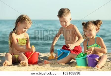 Cute kids building sandcastles on beach