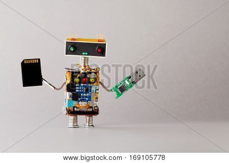 Portable storage devices usb memory card concept. Abstract robot toy with tech accessories. gray background. Macro view copy space