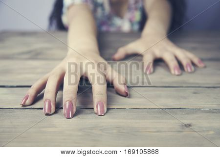 Woman two hands claw at wooden background