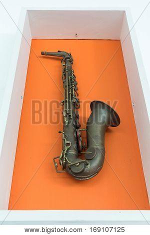 Retro saxophone on orange color wall background