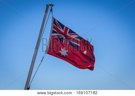 Australian Red Ensign flag on pole against blue sky background