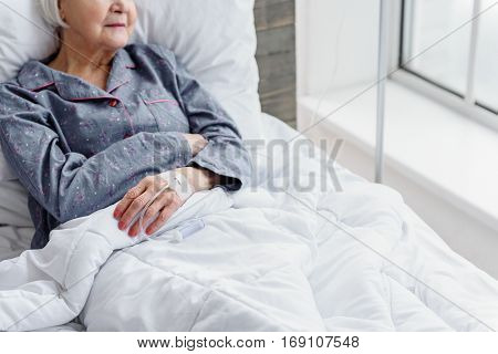 Focus on hand of retiree is on glass-dropper looking at window while reclining on white cot