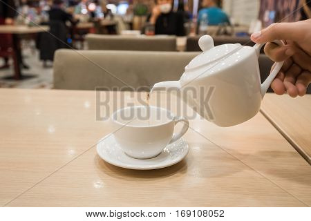 Teapot and cups are prepared for tea drinking in cafe