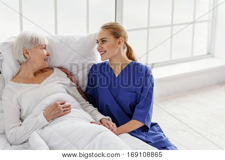 Cheerful therapeutic asking retiree about her general physical and mental state