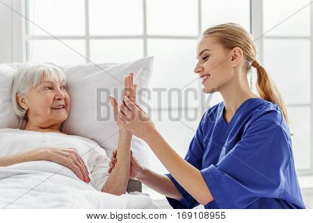 Smiling physician taking pulse rate of pensioner in office of clinic