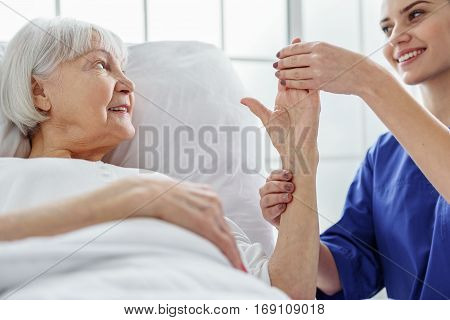 Glad doctor measuring pressure of old patient in hospital room