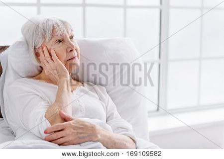Distressed old woman keeping her head while lying up in hospital apartment