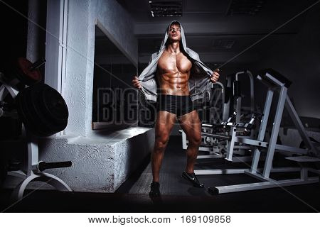 Portrait of a handsome muscular bodybuilder with muscular torso in hoodie posing in gym