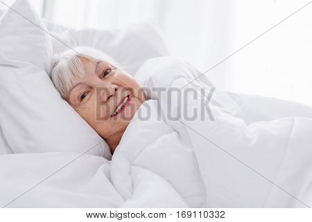 Outgoing pensioner rolling in clean cozy coverlet in hospital room