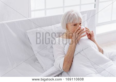 Old woman drinking cup of hot tea while lying in soft white bed near big window