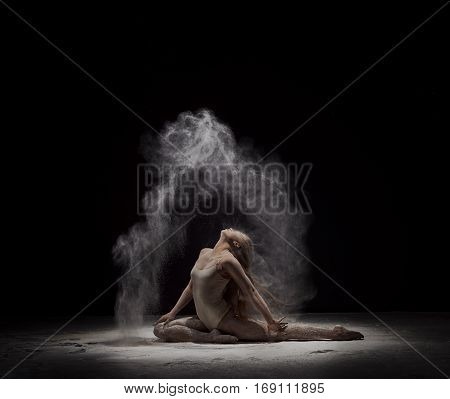 Modern art performance - young flexible dancer performing on dark stage in cloud of white powder, in motion