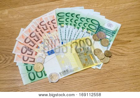 Different Euro Money Of Banknotes And Coins On Wodden