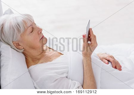 Calm old woman looking at message in mobile while relaxing on comfortable white cot in hospital