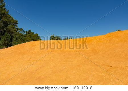 Orange ochre picturesque hills. Village Roussillon Provence France. Preserve natural dye production - ocher.