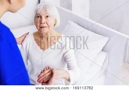 Doctor helping embarrassed grandmother standing up from white cot in apartment of clinic
