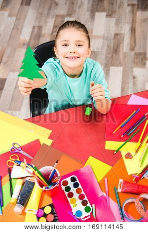 Smiling schoolchild showing green paper fir tree and looking at camera