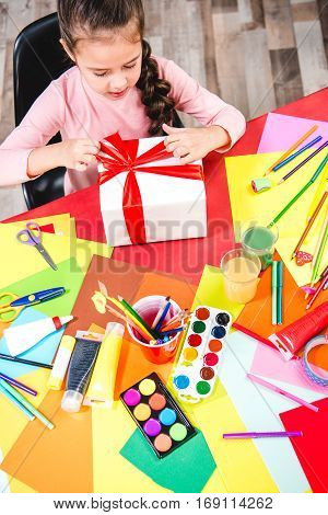 Schoolchild sitting at table with school supplies and wrapping gift box