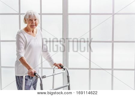 Outgoing old woman standing with foldable walker near wide window in apartment of clinic