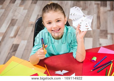 Schoolchild cutting white paper and smiling at camera