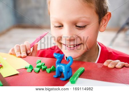 Close-up portrait of smiling schoolchild making toy from plasticine