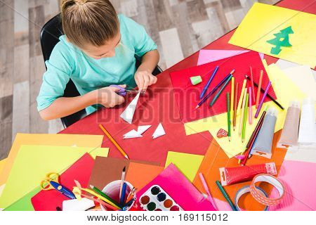 Schoolchild sitting at table with school supplies and cutting white paper
